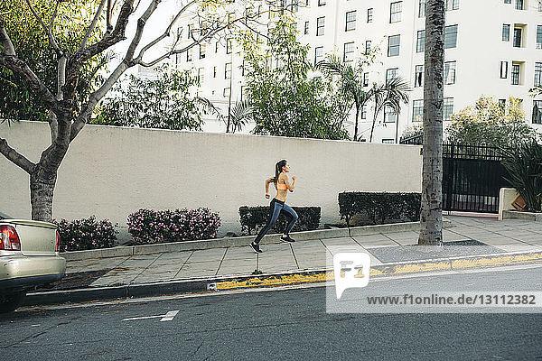 Side view of female athlete running on sidewalk in city