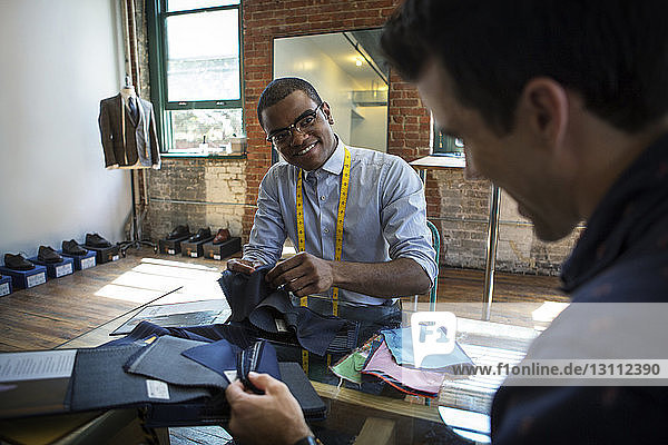 Confident tailor showing fabric swatches at workshop to customer
