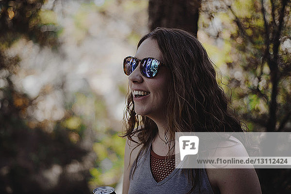 Close-up of happy woman wearing sunglasses while standing in forest