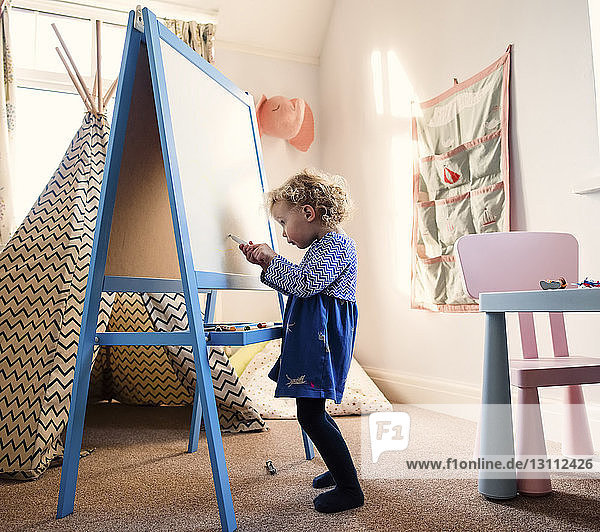 Girl drawing on artist's canvas while standing on rug at home