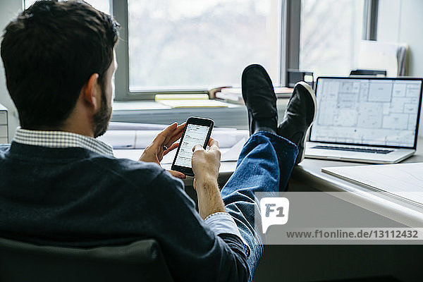 Rückansicht eines Geschäftsmannes  der ein Smartphone benutzt  während er im Büro sitzt