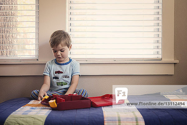 Boy playing with toys while sitting on bed at home