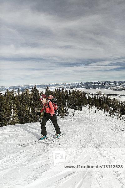 Frau mit Himmel geht auf schneebedecktem Berg gegen wolkigen Himmel im Wald