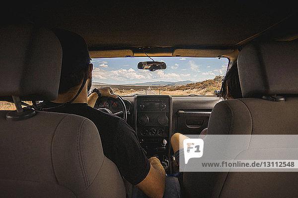 Rückansicht eines Mannes und einer Frau  die in einem Geländewagen auf der Straße unterwegs sind