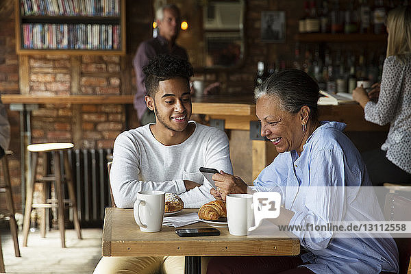 Smiling man looking at woman using phone while customers relaxing at cafe