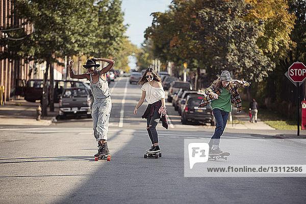 Freunde in voller Länge beim Skateboarden auf der Straße