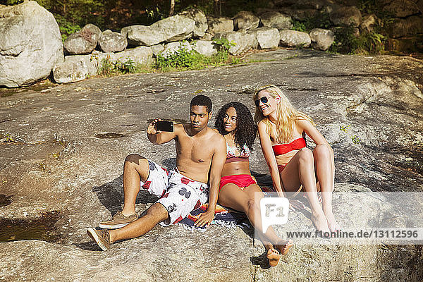 Friends in bathing suits taking selfie through smart phone while sitting on rock during vacation