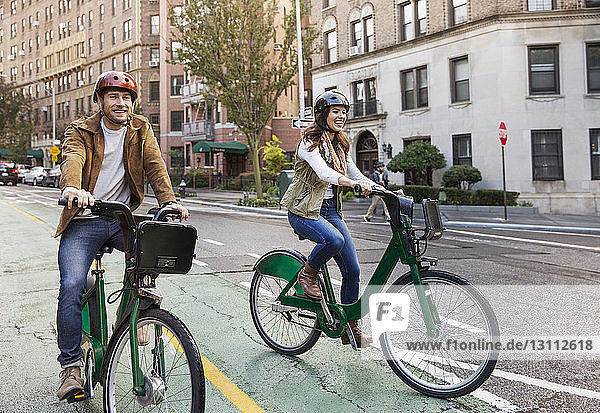 Happy couple riding bicycle on city street
