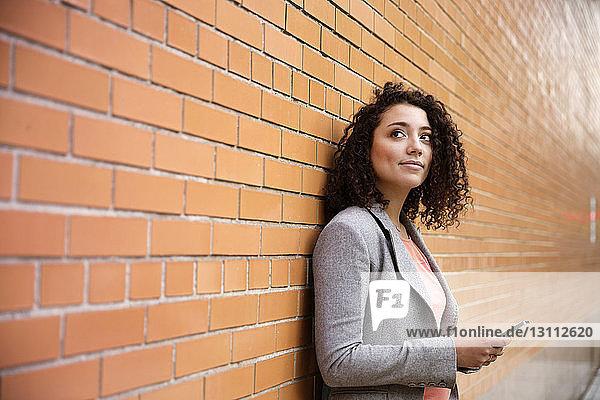 Nachdenkliche Geschäftsfrau hält Smartphone in der Hand  während sie an einer Ziegelmauer steht