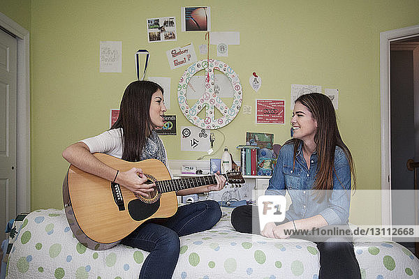 Teenage girl playing guitar while sitting with sister at home