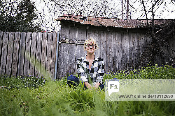Portrait of smiling woman sitting on grassy field in backyard