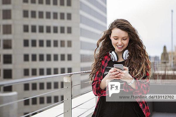 Lächelnde Frau benutzt Smartphone  während sie im Terrassencafé steht