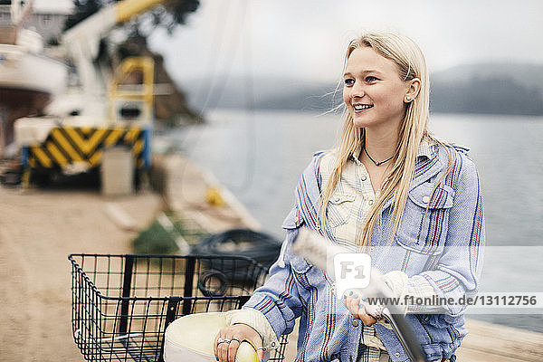 Smiling teenage girl looking away while holding bicycle at harbor