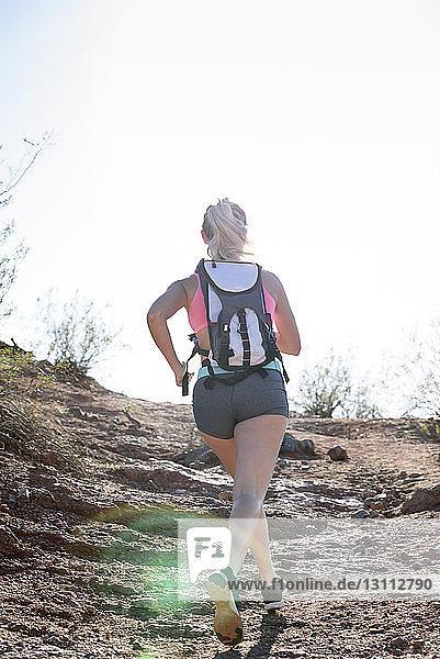 Rückansicht einer Wanderin  die bei Sonnenschein am Berg gegen den klaren Himmel läuft