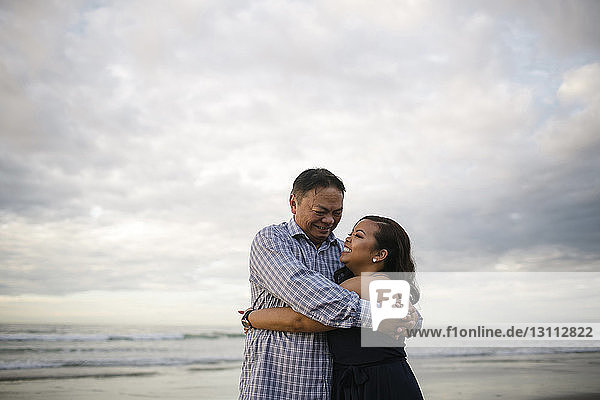 Happy woman embracing father while standing at beach against cloudy sky