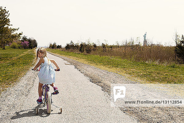 Rear view portrait of girl riding bicycle on road amidst field