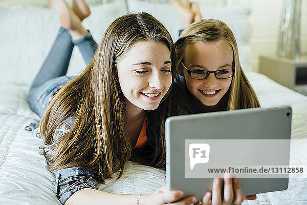 Sisters smiling while using tablet computer on bed