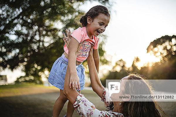 Verspielte Mutter hebt Tochter beim Spielen im Park