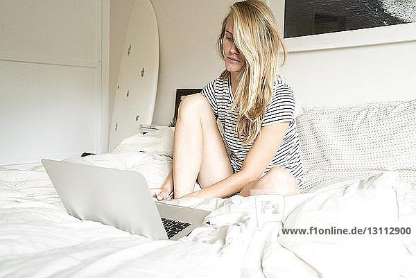 Frau benutzt Laptop-Computer  während sie zu Hause im Bett sitzt
