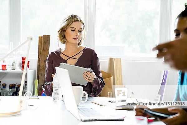 Geschäftsfrau mit Tablet-Computer im Büro mit Kollegen im Vordergrund