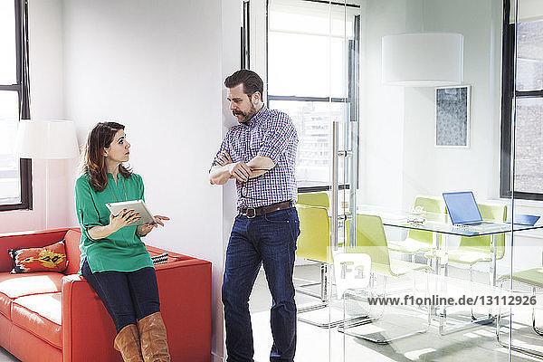Zuversichtliche Geschäftsleute diskutieren über digitales Tablet