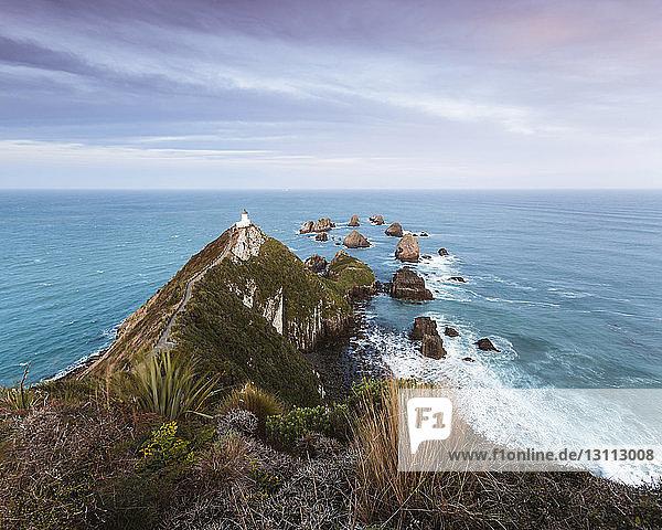 Landschaftliche Ansicht eines Berges am Meer vor bewölktem Himmel