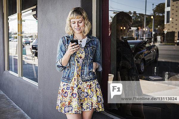 Frau benutzt Smartphone  während sie am Fenster steht
