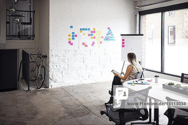 Geschäftsfrau benutzt Tablet  während sie im Kreativbüro sitzt