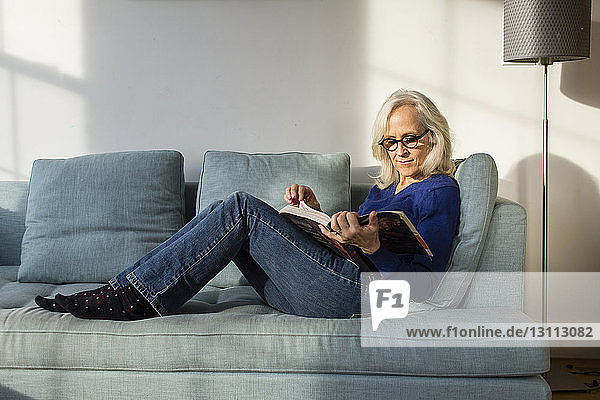 Full length of senior woman reading book while resting on sofa at home