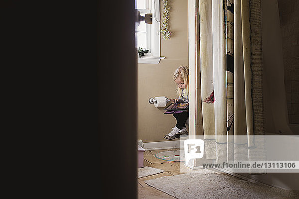 Girl using tablet computer while sitting in bathroom seen through doorway