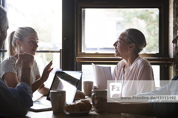 Business people talking while having coffee during meeting at cafe