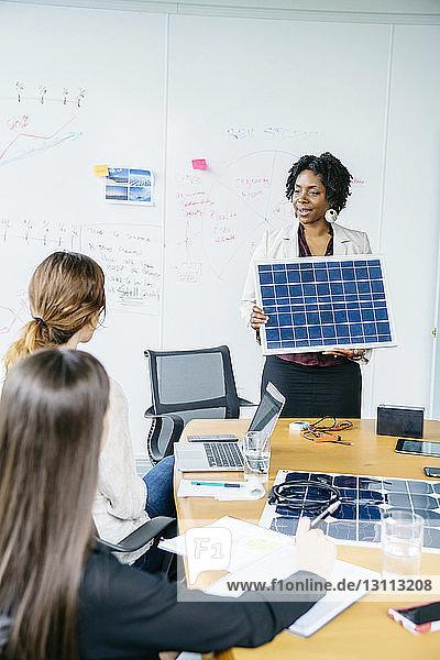 Geschäftsfrau erklärt Kolleginnen während des Treffens das Solarpanel-Modell