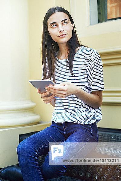 Nachdenkliche Frau  die ein digitales Tablett hält und auf einer Stützmauer sitzt