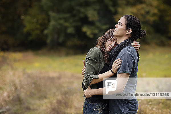 Couple embracing while standing on grassy field