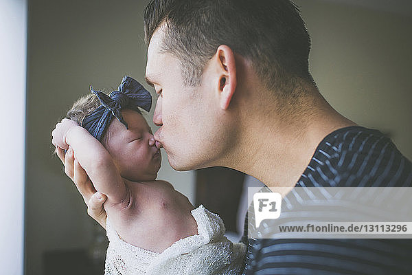 Close-up of father kissing newborn daughter at home