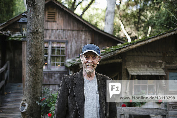 Portrait of man standing against houses