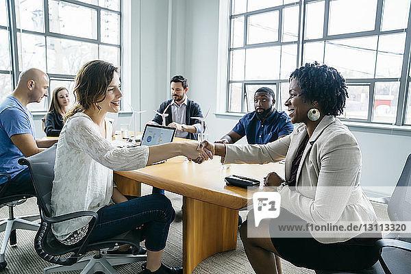 Businesswomen doing handshake during meeting in office