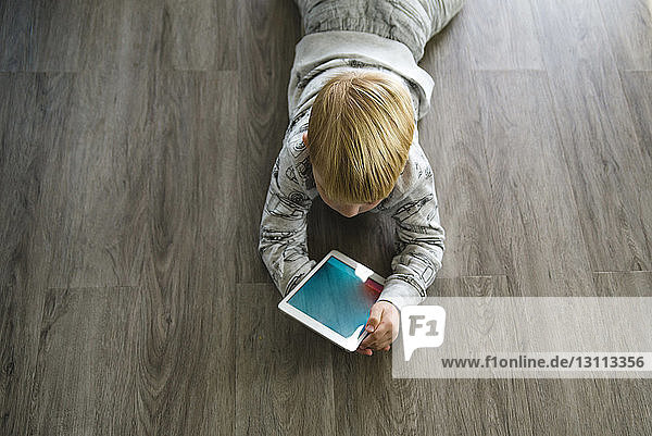 High angle view of boy using tablet computer while lying on floor at home