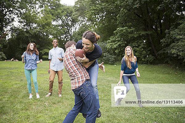 Mann verteidigt Frau mit Fussball in der Hand  während Freunde sie auf dem Feld beobachten