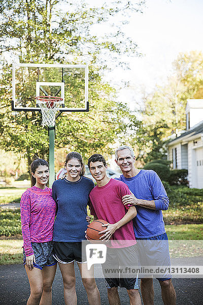 Portrait of family standing against basket ball hoop at backyard