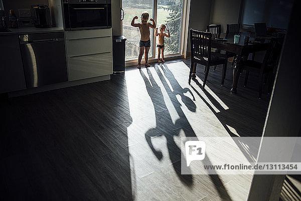 Brüder ohne Hemd  die zu Hause an der Tür spielen und dabei ihre Muskeln spielen
