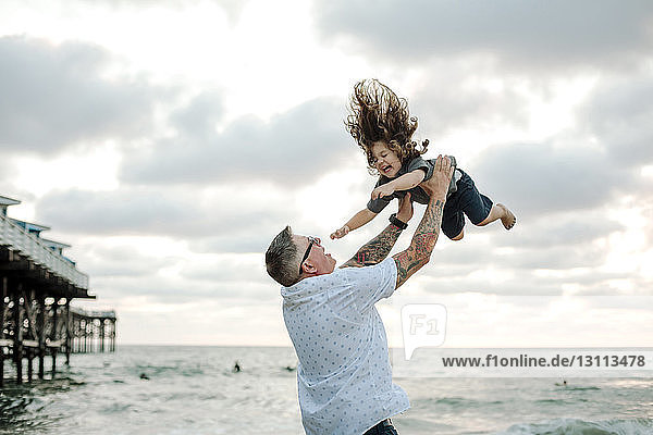 Playful father throwing son in air while playing against cloudy sky at beach