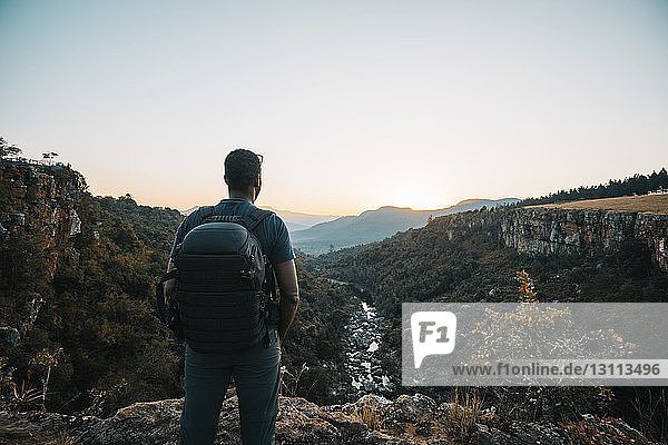 Rückansicht eines Mannes mit Rucksack  der bei Sonnenuntergang auf einem Berg vor klarem Himmel steht