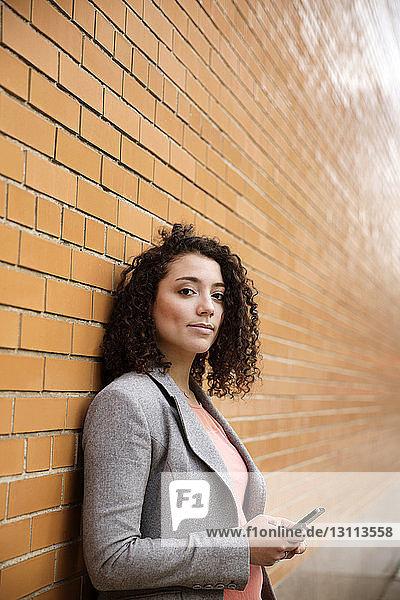Porträt einer selbstbewussten Geschäftsfrau  die ein Smartphone an einer Ziegelmauer hält