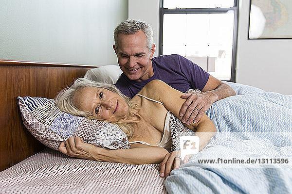 Porträt einer selbstbewussten Frau mit zu Hause auf dem Bett liegendem Mann