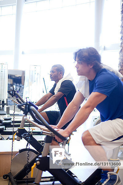 Side view of men riding exercise bikes in gym