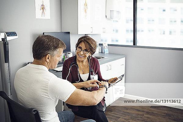Glückliche Ärztin diskutiert mit männlichem Patienten in der Klinik