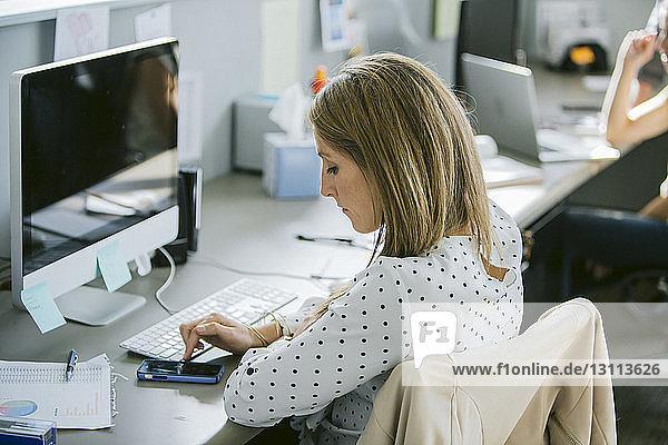 Geschäftsfrau benutzt Mobiltelefon  während sie mit einem Kollegen am Schreibtisch sitzt