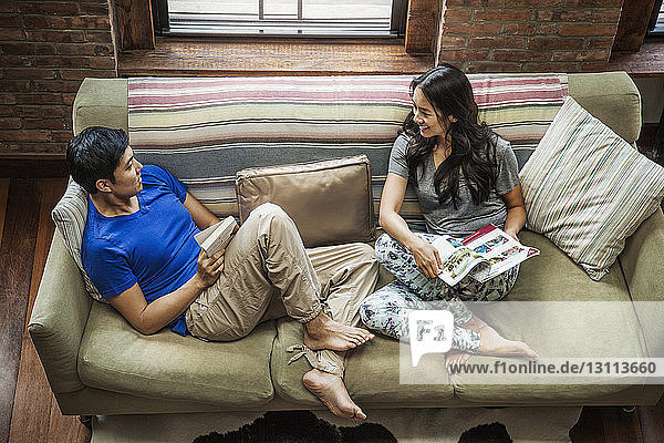 High angle view of couple sitting on sofa at home