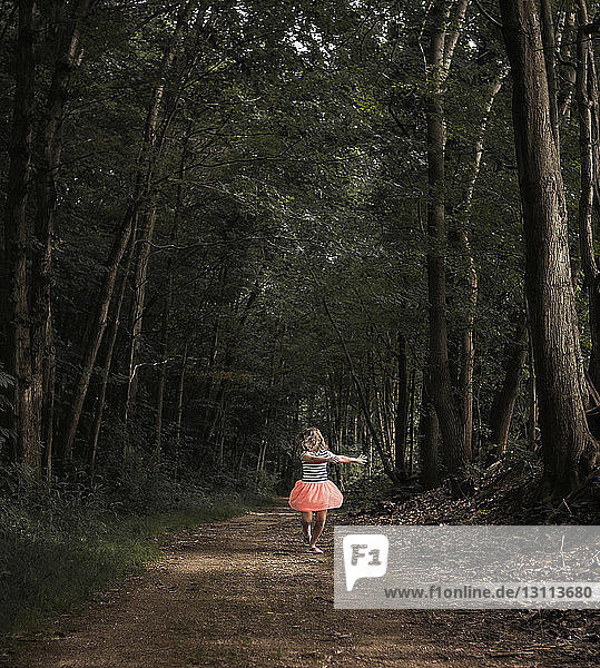 Girl dancing on dirt road amidst forest